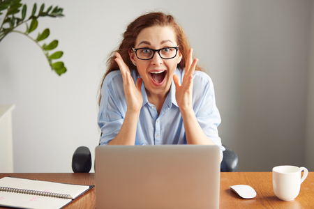 Photo pour Portrait of a cute redhead girl wearing glasses and blue shirt screaming with excitement and joy while working on her laptop. Headshot of an excited female student with winning expression on her face - image libre de droit