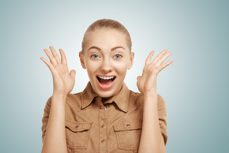 Close up studio portrait of happy excited woman celebrating her success with mouth wide open in excitement against blue wall background. Human emotions, facial expression, feelings, life perception