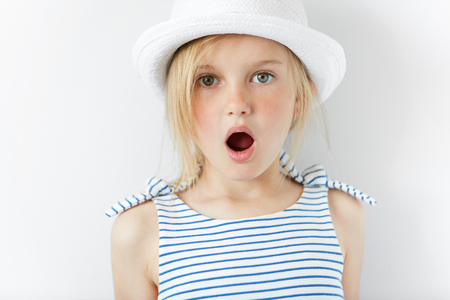 Close up portrait of amazed adorable little girl in white hat and striped dress, having fun indoor, looking at the camera in excitement, astonished with something. Human face expressions and emotionsの写真素材