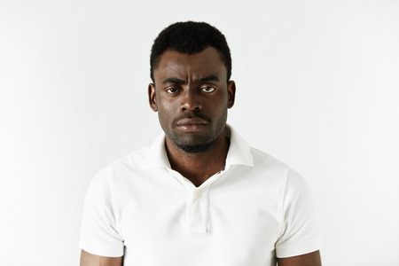 Portrait of angry or annoyed young African American man in white polo shirt looking at the camera with displeased expression. Negative human expressions, emotions, feelings. Body language
