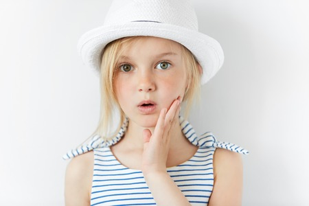 Portrait of surprised or frightened girl looking at the camera with a hand on her cheek. Close up shot of blonde Caucasian little girl with scared or shocked expression against white studio wallの写真素材