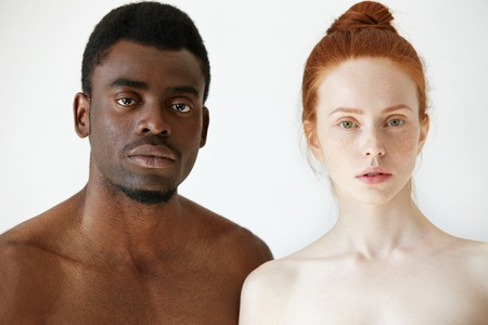 True love between two young people of different races. Headshot of freckled redhead Caucasian woman and African man posing shirtless against white concrete wall background, looking at the camera