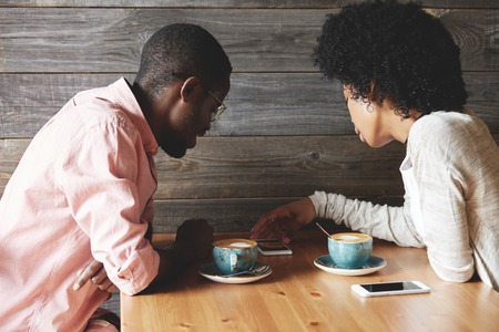 Love and relationships. Lovely young African American couple having a date at a coffee shop, drinking cappuccino, watching photographs on mobile phone, while sitting at the wooden table. Back viewの写真素材