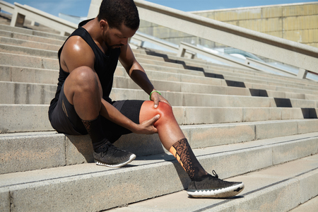 Physical injury concept. Attractive African runner with athletic body wearing black running shoes, sitting on steps on concrete stair, clutching injured knee in excruciating pain depicted in red color