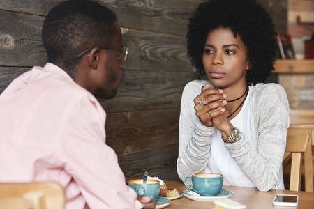 Photo for Close up portrait of African American friends at cafe having serious conversation, fashionable hipster woman with Afro hairstyle looking at her boyfriend with puzzled and thoughtful face expression - Royalty Free Image