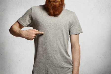 Photo pour Design and advertising concept. Cropped shot of stylish young man with hipster red beard pointing index finger at copy space on his casual gray t-shirt, standing indoors against concrete wall - image libre de droit