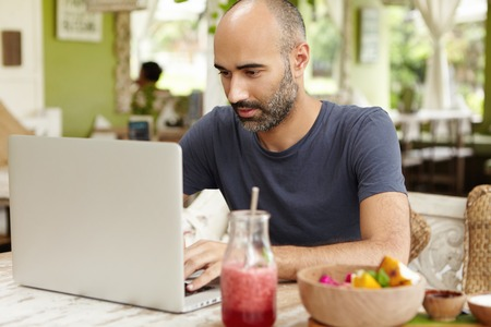 Bearded middle-aged self-employed man sitting at cafe in front of generic laptop and looking at screen with serious and concentrated expression while working remotely on his project, using free wifi