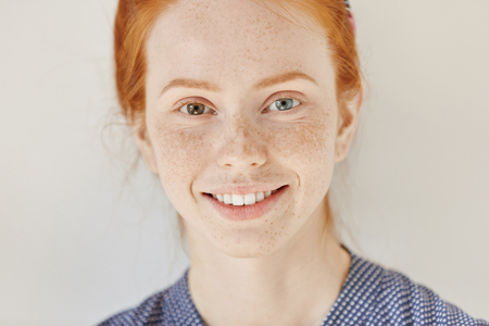 Photo pour Close up portrait of beautiful young redhead model with different colored eyes and healthy clean skin with freckles smiling joyfully, showing her white teeth, posing indoors. Heterochromia in human - image libre de droit