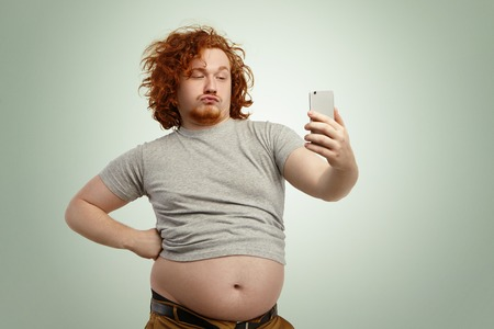 Photo pour Funny overweight plump man with duck lips wearing undersize t-shirt with belly hanging out of pants, keeping hand on waist, posing for selfie, holding cell phone, trying to seem attractive and sexy - image libre de droit