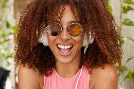 Photo pour Photo of joyful stylish teenager with Afro haircut, dark skin, opens mouth widely, smiles positively, wears round sunglasses, listens music with new modern headphones, feels content, enjoys melody - image libre de droit