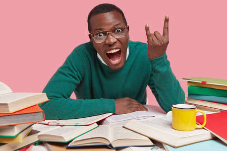 Hey, its cool. Dark skinned student makes rock n roll gesture, exclaims loudly with widely opened mouth, wears green sweater, surrounded with books, yellow mug of drink, isolated over pink background