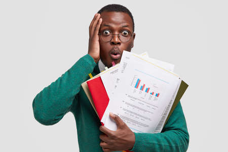 Photo pour Headshot of puzzled African American man touches head, stares with bugged eyes, opens mouth from amazement, holds paper documents, has deadline for making task, isolated on white studio wall - image libre de droit