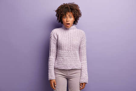 Photo pour Studio shot of stunned pretty Afro American female entrepreneur surprised to fail, looks at camera surprisingly, has rush reaction, dressed in winter sweater, isolated over purple studio wall - image libre de droit