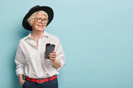 Foto de Portrait of happy elderly woman being on pension, has meeting with former colleagues, holds takeaway coffee, wears stylish white shirt, trouses with red belt, keeps hand in pocket. Leisure, retirement - Imagen libre de derechos
