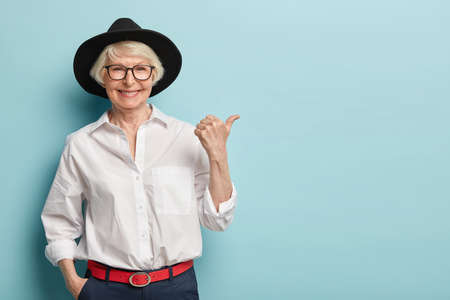 Photo pour Waist up shot of friendly looking senior lady in stylish headgear, white elegant shirt and formal trousers, holds hand in pocket, points thumb away, has happy smile, advertises something nice - image libre de droit