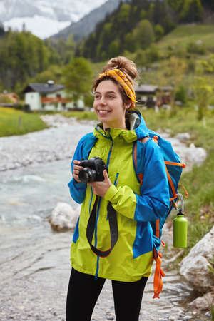 Photo pour Optimistic lovely female hiker walks by small mountain stream, holds professional photo-camera, makes photos of landscape, green forest and small house behind - image libre de droit