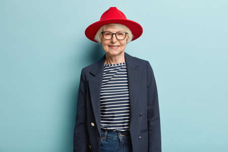 Photo pour Fashionable grey haired lady with wrinkled face, wears red stylish hat, jacket and jeans, has pleasant smile, feels self assured in her beauty, isolated on blue background, has happy relaxed look - image libre de droit