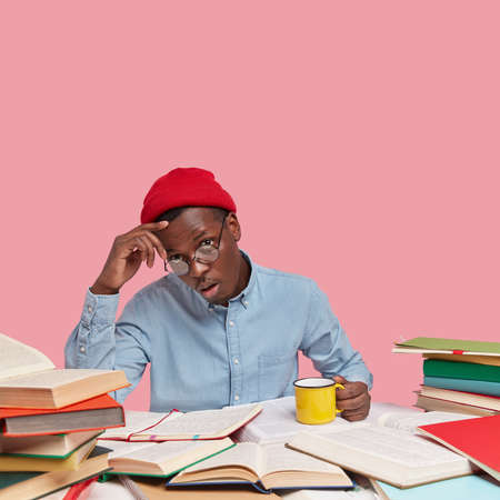 Puzzled dark skinned man keeps hand on head, has tired facial expression, wears formal shirt and red headgear, enjoys hot drink, borrows many books from library isolated over pink wall with free space
