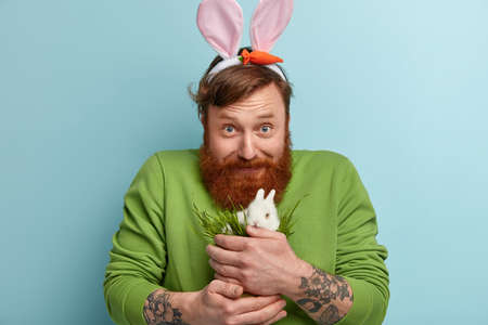 Photo pour Horizontal shot of satisfied blue eyed bearded guy feeds small white rabbit with green grass, loves pet, wears casual jumper, bunny ears, looks gladly at camera, cares about animal, stands indoor - image libre de droit