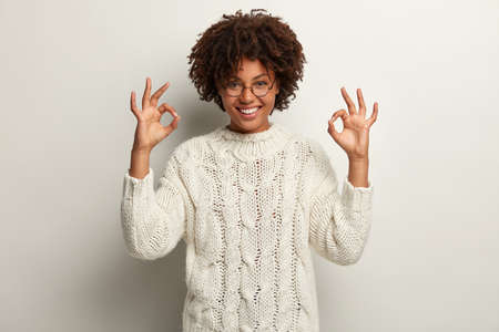 Photo for Approval and agreement concept. Picture of happy black ethnic woman makes okay gesture with both hands, says everything is super or perfect, dressed in white jumper, proceeds according to plan - Royalty Free Image