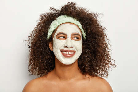 Photo pour Headshot of lovely dark skinned curly woman applies clay mask for refreshing skin, looks gladfully aside, has charming smile, stands topless against white background. Personal care, cosmetology - image libre de droit