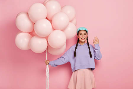 Photo for Positive Chinese woman comes on friends birthday party, greets fellows, has dark hair combed in two plaits, dressed in casual outfit, holds helium balloons, poses over pink studio wall - Royalty Free Image
