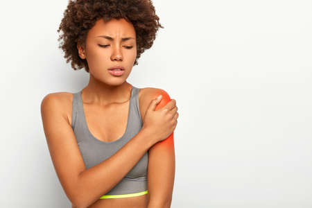 Photo pour Horizontal shot of dissatisfied Afro woman touches red shoulder, stretched muscles during sport training, has sad expression, wears grey bra, isolated over white background. Health problems. - image libre de droit