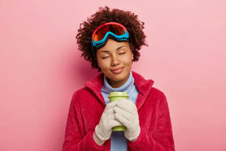 Photo pour Photo of lovely female traveler enjoys winter time, drinks coffee, has eyes shut, imagines something pleasant, snowboarding activities with friends, smiles gently, poses indoor. Pastime, recreation - image libre de droit