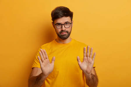 Photo pour Slow down. Serious looking displeased bearded man shows stop gesture, asks to hold horses, keeps palms towards camera, says take it easy and control your behaviour, stands against yellow background - image libre de droit
