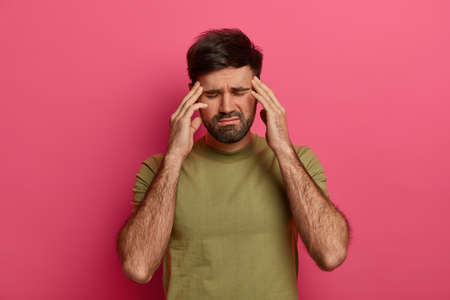 Photo pour Exhausted man touches temples with closed eyes, suffers from headache, waits someone bring painkillers, wears t shirt, has bad day, isolated over pink background, bothered with painful disease - image libre de droit