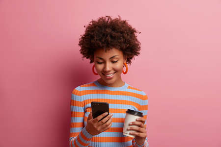 Photo pour Portrait of happy young African American woman types message, uses new mobile application, searches web and drinks takeaway coffee, has positive expression, wears striped jumper, stands indoor - image libre de droit