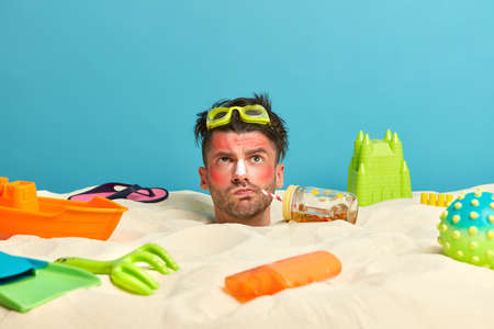 Photo for Head of man with thoughtful expression, buried in sand, drinks refreshing beverage, uses sunblock, spends much time at sandy beach near sea, got very bad sunburn, surrounded by different items - Royalty Free Image
