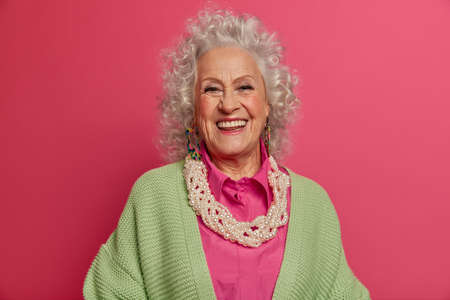 Photo pour Headshot of good looking elderly woman smiles broadly, makes photo for long memory, being in happy mood, dressed in elegant clothes, isolated on pink background. Beauty, style, age, fashion concept - image libre de droit