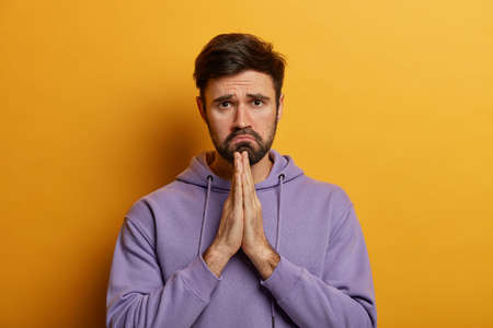Photo for Whining gloomy man with sad expression presses palm in pray, says please, begs for favour, badly needs help, asks for apologize, wears purpe hoodie, poses against yellow studio wall. Help me - Royalty Free Image