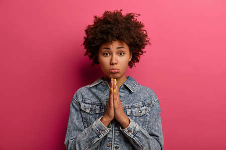 Photo for Innocent girl needs help, has miserable hopeful face expression, purses lower lip and pressed palms together, begs or pleads for favor, wears denim jacket, asks to lend money, has imploring gaze - Royalty Free Image