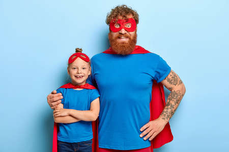 Photo pour Family portrait of funny father and daughter play superhero, pretend being superpowerful, cuddle indoor, wears special costumes with mask and cape, isolated on blue background. Children holiday - image libre de droit