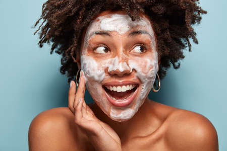 Photo pour Headshot of happy black woman with foam or foaming cleanser on face, has facial treatments, gazes aside, opens mouth, has Afro hairstyle, isolated over light blue wall. Perfect clean skin concept - image libre de droit