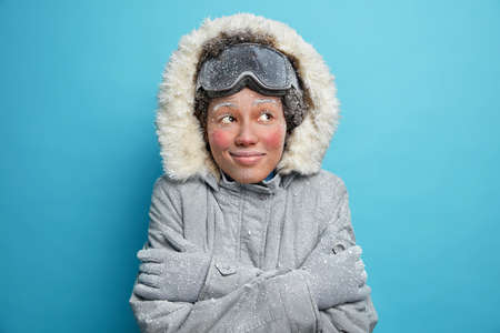 Foto de Frozen woman embraces herself trembles from cold covered with hoarfrost looks gladfully wears snowboard goggles winter jacket and gloves smiles pleasantly isolated over blue studio background - Imagen libre de derechos