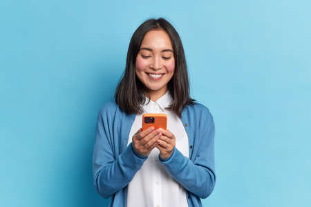 Photo pour Smiling charming brunette Asian woman uses mobile phone happy texting in social networks addicted to modern technologies wears casual jumper isolated over blue background. Online communication - image libre de droit