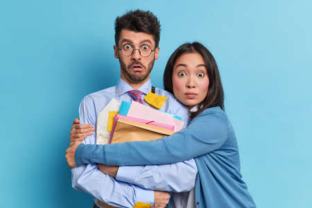 Photo for Emotional shocked woman and man partners stare stunned at camera meet to discuss working plan study project together. Scared Asian female embraces groupmate afraid of passing exam. Two colleagues - Royalty Free Image