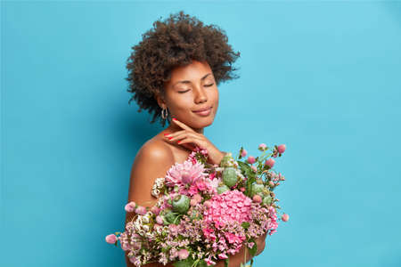 Photo pour Pleased gentle female model touches jawline closes eyes enjoys lovely moment poses half naked with bunch of beautiful flowers isolated over blue background. Ethnic woman with bouquet poses indoor - image libre de droit