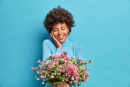 Photo pour Portrait of pleased curly haired young African American woman closes eyes from pleasure touches cheek gently smiles tenderly happy to get flowers isolated over blue background. Women Day concept - image libre de droit
