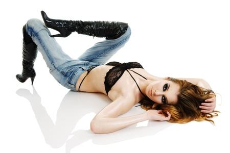 Foto de Seductive young woman wearied in black lingerie lying down on floor isolated over white background - Imagen libre de derechos