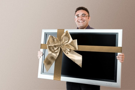 Man holding in hands lcd tv with flat screen and golden bow