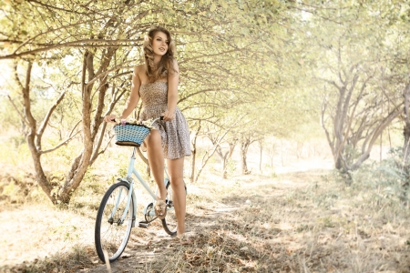 Photo for Young woman with retro bicycle in a park - outdoor portrait - Royalty Free Image