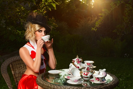 Young woman posing as magnificent card queen from wonderland at mystic tea-party
