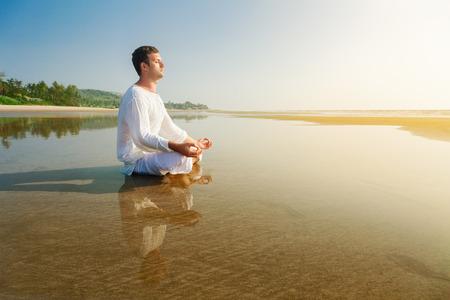 Man doing yoga asana meditating in a lotus position
