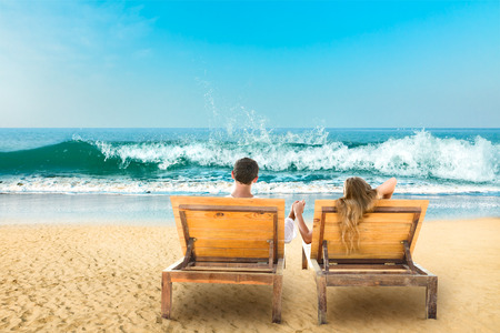 Young couple relaxing lying down on a beach chair