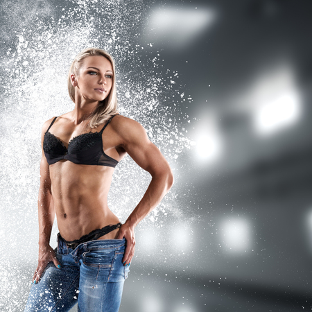 Bodybuilder athletic woman in bikini showing her muscles