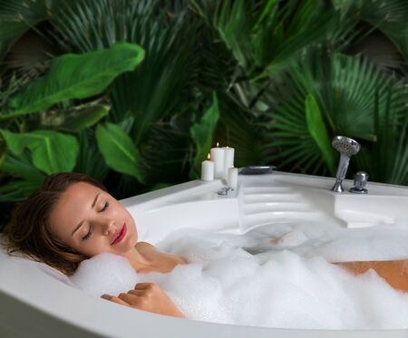 Foto de A woman relaxes in hot bath tub with soap foam. Luxury spa interior of bathroom with tropical plants leaves. - Imagen libre de derechos